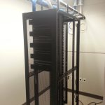 The server room contains the enclosed server cabinet. The side panels are removed in this picture as we were punching down cables onto the backs of the patch panels.